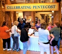 People at a registration table for Pentecost celebration