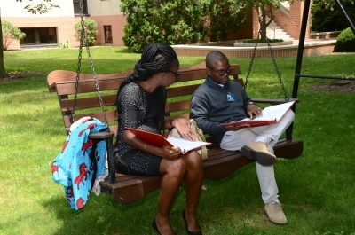 Black couple studying the Bible together on a bench outside