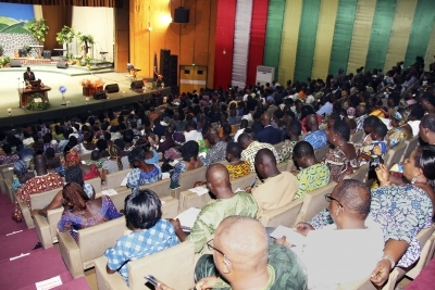Person standing at lectern with large audience in Togo