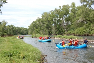 Group of rafts going down the Gunnison River at Camp Gunnison—The Way Household Ranch
