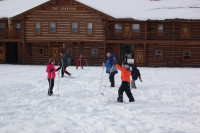 People playing on skis in the snow at Camp Gunnison—The Way Household Ranch
