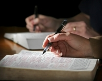 Two people studying their Bible with pen in hand—only hands visible