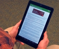 Person holding a tablet with a web article on it