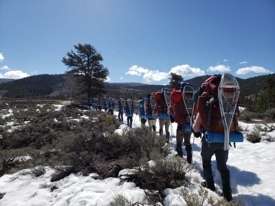 Line of people hiking down a trail in the snow