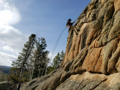 Person rappelling down a rock face